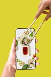 Order sushi set using mobile phone app. Online food delivery concept.