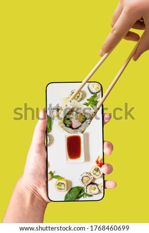 Order sushi set using mobile phone app. Online food delivery concept.