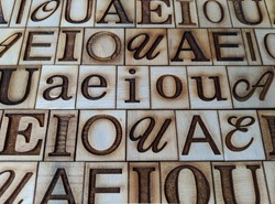 ordered vowels capital and lowercase engraved on pieces of wood