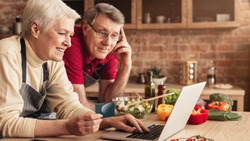 Ordering Food Online. Smiling elderly couple with laptop and credit card purchasing grocery delivery from internet while cooking together in kitchen