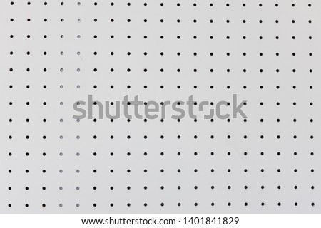 orderly holes or dot rows and columns on white pegboard wall. Stock photo ©