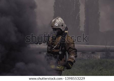 ordinary firefighter in a smoke-filled environment, moving in on the firing line
