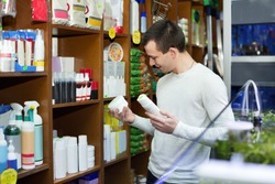 Ordinary male customer buying flea treatment and shampoo in petshop