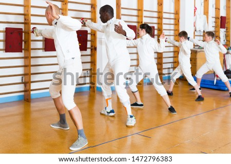 Ordinary mixed age group of athletes at fencing workout, training attack movements on mannequins #1472796383