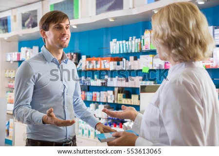 Ordinary positive male talking to pharmacist at pharmacy