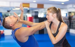 Ordinary woman is fighting with trainer on the self-defense course for woman in sport club