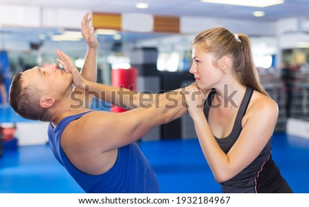 Ordinary woman is fighting with trainer on the self-defense course for woman in sport club Stock photo ©