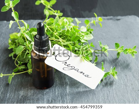 Oregano oil bottle with label and oregano herb bunch #454799359