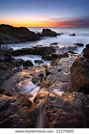 Oregon coastal scene, including a stream, the ocean, and sunset.