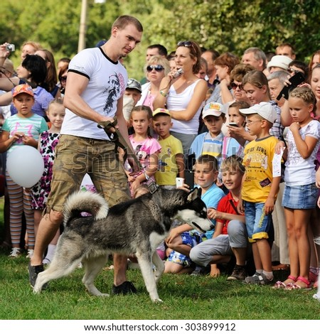 Orel, Russia, August 01, 2015: Mumu Fest, Turgenev\'s story art-festival, man with husky, childrens looking at the dog