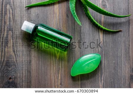Organic aloe vera cosmetics. Aloe vera leafs, glass of aloe vera juice and soap on wooden table background top view #670303894