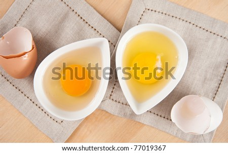 Organic and Conventional Raw Eggs in Small White Bowls