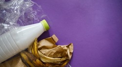 organic and inorganic waste. plastic waste and banana peel. purple background copy space right