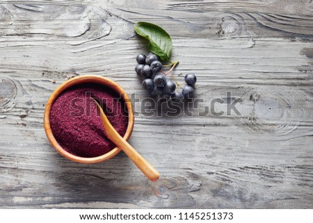 Organic Aronia powder in a bowl with fresh aronia berries on table.  #1145251373