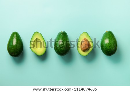 Organic avocado with seed, avocado halves and whole fruits on blue background. Top view. Pop art design, creative summer food concept. Green avocadoes pattern in minimal flat lay style