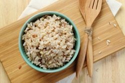 Organic Brown Rice in the bowl on the wooden table