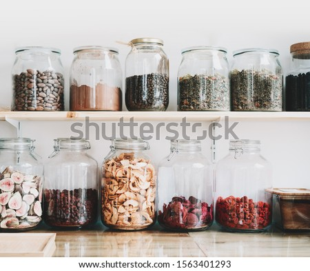 Organic bulk products in zero waste shop. Foods storage in kitchen at low waste lifestyle. Dried berries and fruits in glass jars on shelves. Eco friendly shopping in plastic free grocery store.
