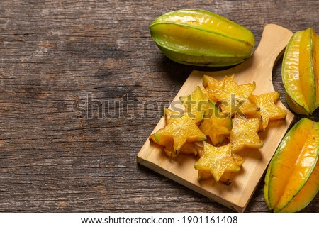 organic carambola asian fruit, star fruit, grown on organic farm in a wicker basket on a rustic wooden table top view with space for writing Сток-фото ©
