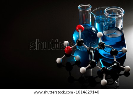 Organic chemistry, science class and STEM research concept with a methyl benzoate molecule on blue chemical solution in chemistry glassware, Erlenmeyer and Boiling (or Florence) flasks with copy space #1014629140