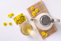 Organic Chrysanthemum flower tea in a cup and teapot on white background, Healthy Herbal drink, Top view
