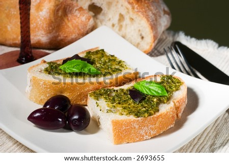 Organic ciabatta bread with pesto dressing and black olives
