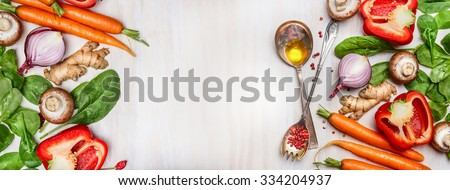 Organic clean vegetables assorted with cooking spoons and oil on white wooden background, top view, banner. Healthy  food, vegan or diet nutrition concept.