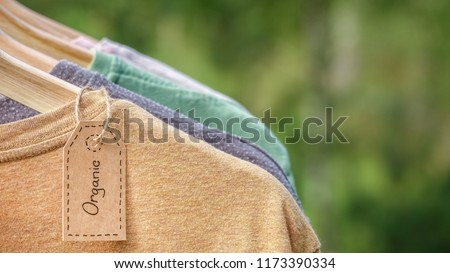 Organic clothes. Natural colored t-shirts hanging on wooden hangers in a row. Eco textile tag. Green forest, nature in background. #1173390334