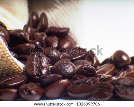 Organic coffee beans in sack and wooden coffee dipper on white background close up isolated. #1026399706