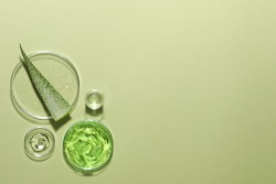 Organic cosmetic product, natural ingredients and laboratory glassware on green background, flat lay. Space for text