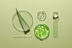 Organic cosmetic product, natural ingredients and laboratory glassware on green background, flat lay