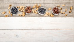Organic dark and yellow raisins in glass bowls on wooden table background.