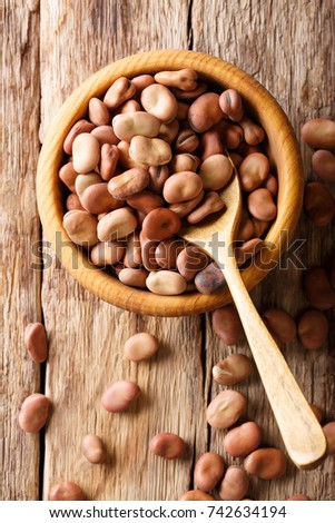 Organic dried broad beans close-up in a wooden bowl on a table. Vertical top view from above