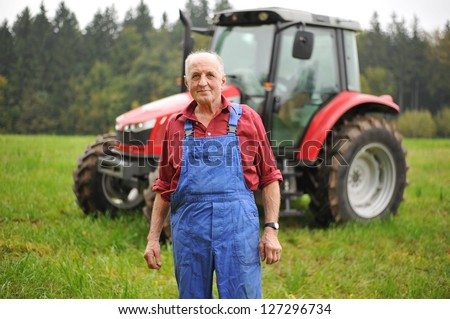 Organic farmer standing in front of his red tractor