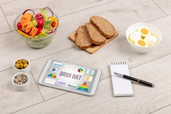 Organic food and tablet pc showing DASH DIET inscription, healthy nutrition composition