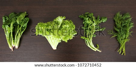 Organic food background. Spring vitamin set of various green leafy vegetables on rustic wooden table. Fresh spinach, lettuce leaves, dill on wood table. Top view. - Shutterstock ID 1072710452