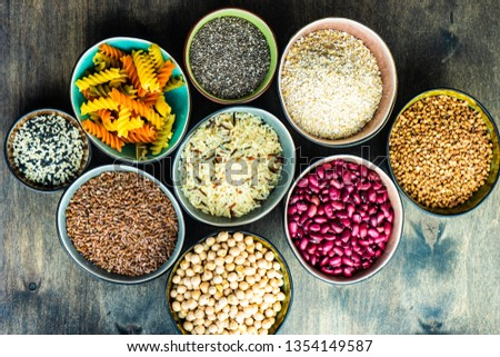 Organic food concept with different types of cereals in ceramic bowls on wooden background with copy space #1354149587