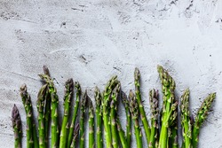 Organic fresh asparagus over concrete textured background, top view, space for text.