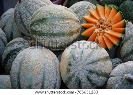 Organic Fresh Cantaloupe melon sale in the market.cantaloupe melon on hay grass background.Fruit and healthy care concept.