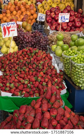 Organic Fruits in a Traditional Bazaar in Iran. Translation of Price Tags: Strawberries of Sanandaj City, 12000 Tomans per Half a Kilo - Grapes of Shahroud, 15000 Tomans - Black Plumes, 15000 Tomans Imagine de stoc ©