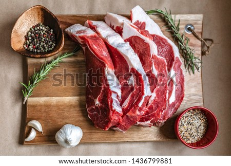 Organic grass-fed ribeye steak on wood board, paper background species. Beef Meat, raw meat. Canadian organic ribeye steak with an amazing taste. Ribeye is GMO, Steroid, Hormone and Antibiotic Free
