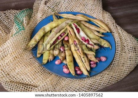 Organic green beans shelled and in pod on blue plate, tow and wood