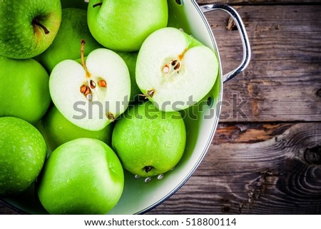 organic green juicy apples in colander on rustic wooden background