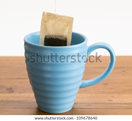 Organic green tea or herbal tea being lowered into a blue mug on wooden table