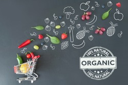 Organic grocery shopping cart filled with fruits and vegetables and sketches on a chalkboard