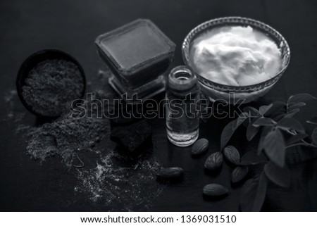 Organic hair conditioner on wooden surface i.e. Hing or devil's dung and almond oil with yogurt in a glass bowl and all the raw ingredients present on the surface with some rose leaves. Photo stock ©