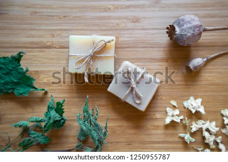 Organic handmade soap making, spa treatments, skin care. Spa soap bars with natural ingredients.  Dried herbs, oats and rose blossoms on wooden vintage background. Instagram style, top view photos.