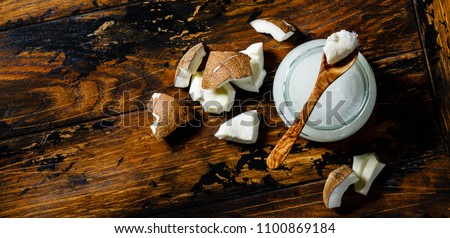 Organic healthy Coconut butter and fresh coconut pieces on wooden background copy space #1100869184