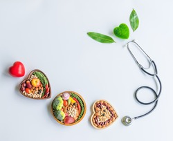 Organic  healthy  food,fruits,vegetables  in  wooden  bowl,stethoscope,red,green  heart  shape  and  leave  herb  on  white  background  for  creative  healthcare  and  ecology  concept