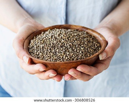 Organic Hemp Seeds. A woman holding a wooden bowl of hemp seeds.
