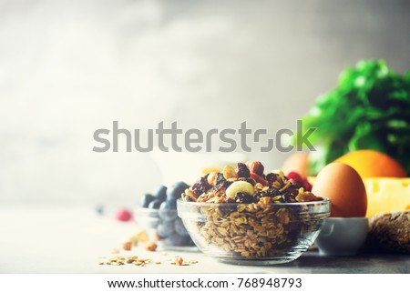 Organic ingredients for healthy lunch - berries, milk, egg, oatmeal on grey concrete background. Copy space. Healthy breakfast concept.
